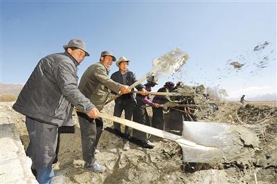 日喀则市江孜县江热乡让康村村民正在一铲接一铲地将水渠内的淤泥清理出来。