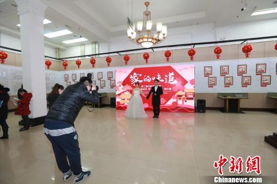 沈阳:新人拍婚照 选择家风展板当背景