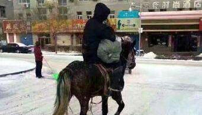 """""""敬业快递哥"""" 快递小哥雪天骑马送快递"""
