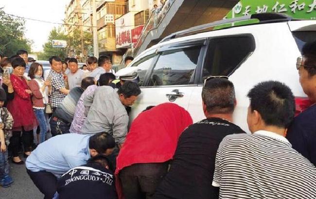 阜阳临泉闹市区 众人抬车救人