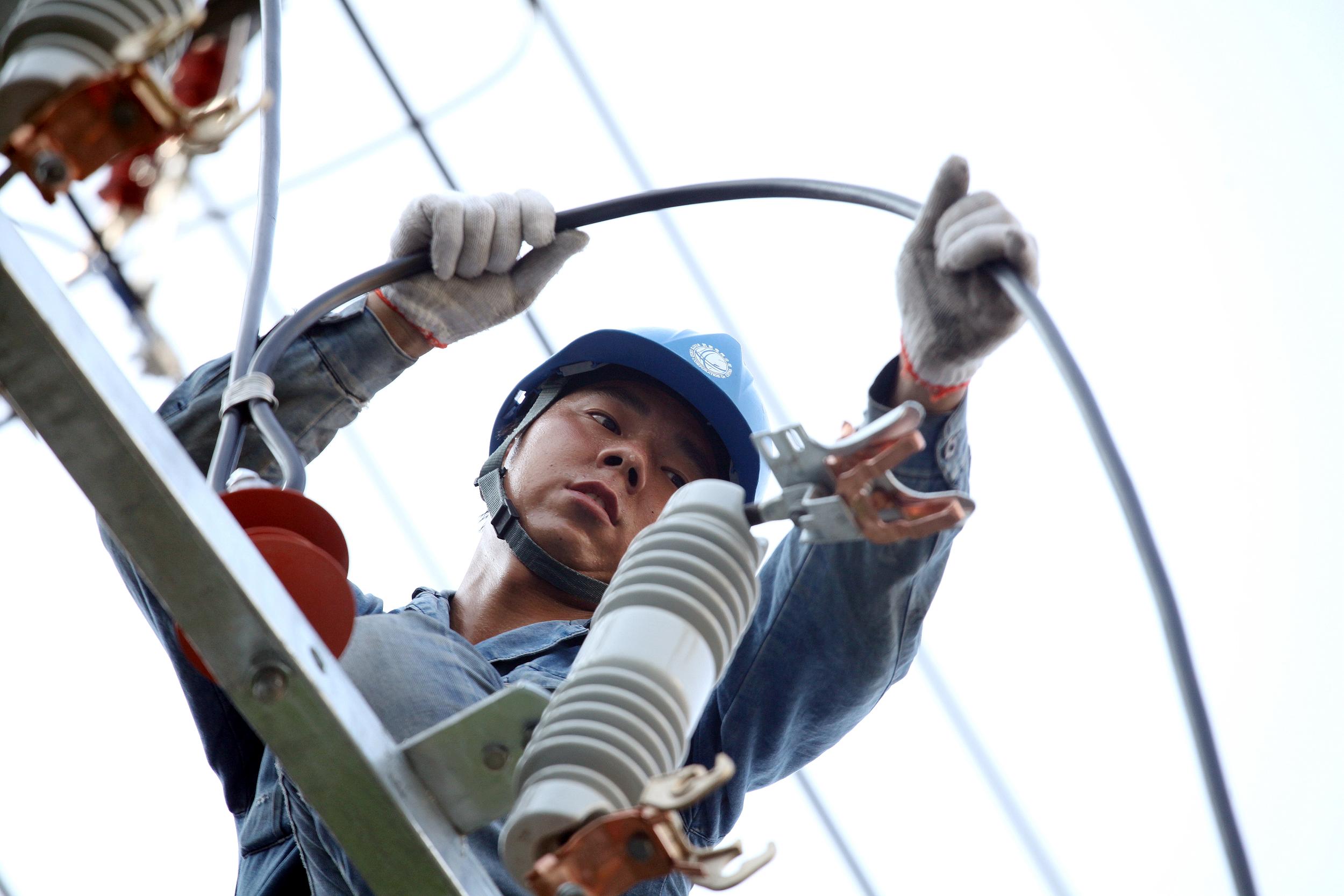 图为电力施工人员正在配变台架安装变压器熔断器并连接导线。7月29日,安徽临泉县供电公司的电力施工人员在近40度的高温天气下,为城区港口南路紧急新增一台容量为400千伏安的配电变压器,及时消除该区域低电压问题,确保周围居民和商户的正常用电。图为,临泉供电公司的电力施工人员正在配变台架上进行新装变压器进行高低压导线的连接工作。