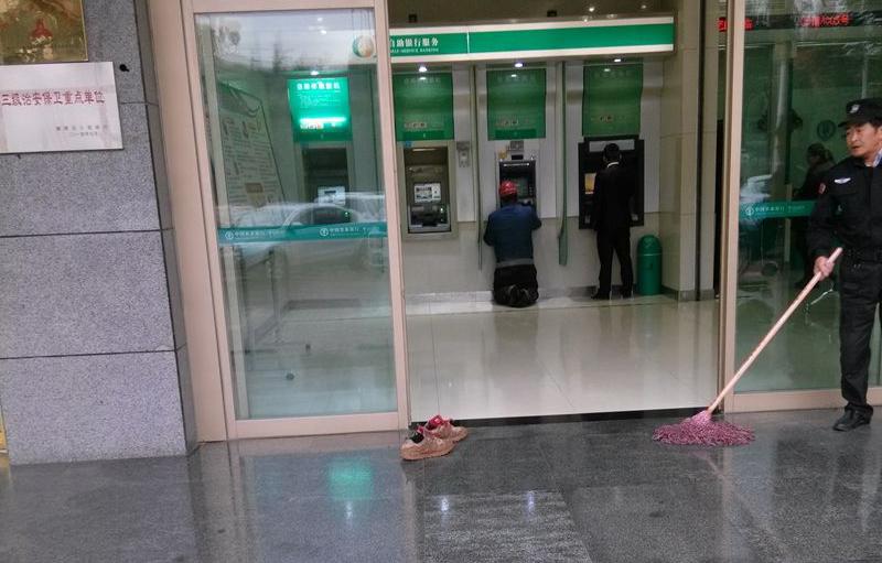 西安一农民工怕弄脏地面 脱鞋跪地在ATM机前取款