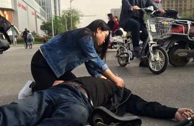 西安老人骑车晕倒在地 路过女孩急救跪地做人工呼吸
