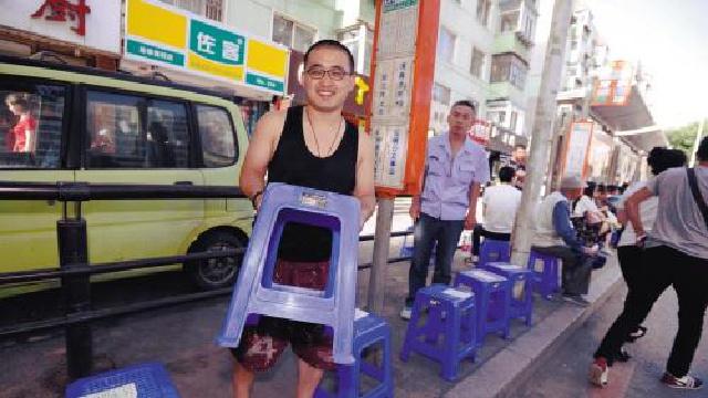 沈阳:266路公交站整齐摆放着21个爱心凳