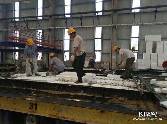 合创建筑节能生产车间工人正在运用新建材生产装配式框架结构.
