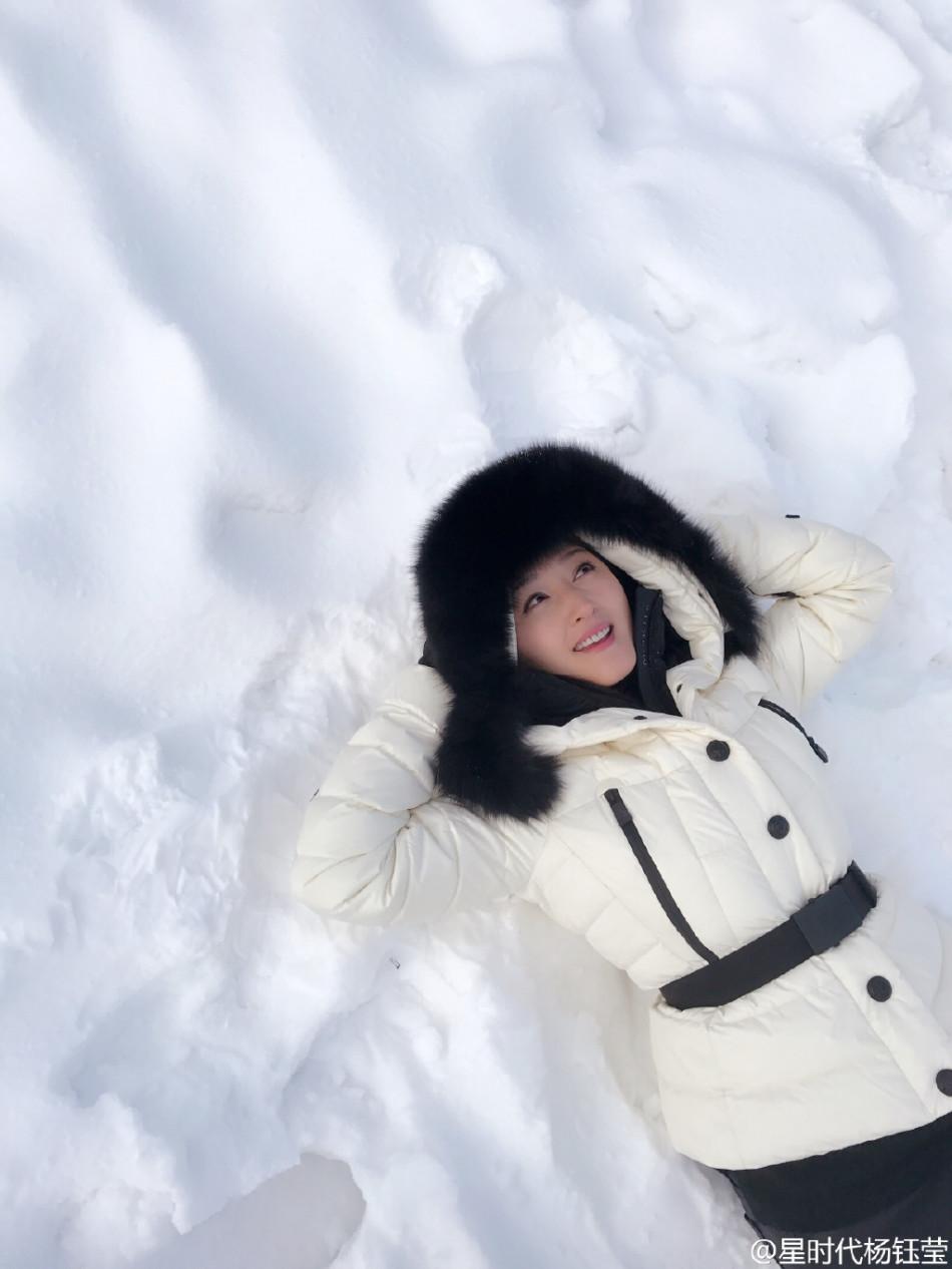 杨钰莹微博发出一组照片,穿着白衣躺在雪地上,戴麋鹿发卡扮可爱.